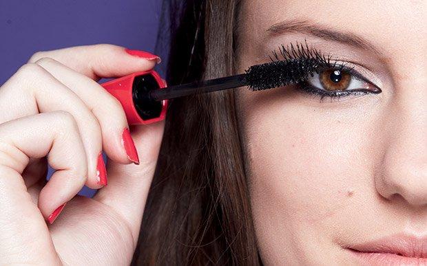 garota aplicando mascara de cilios
