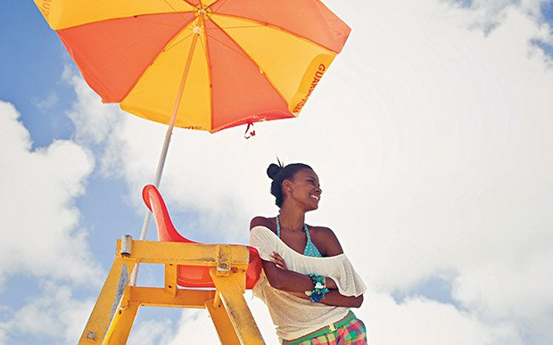garota na praia sob um guarda sol