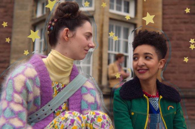 Duas meninas se olham na escola depois de descobrirem que estão apaixonadas uma pela outra. Elas vestem roupas coloridas. Uma é branca e a outra é negra.