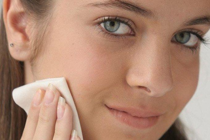 garota limpando pele demaquilante