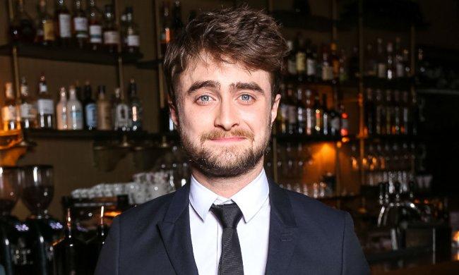 Daniel Radcliffe sorrindo levemente para direção da câmera usando terno preto e gravata preta com uma camisa branca com uma parede de pedidas de fundo