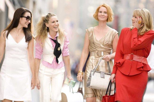 Imagem das quatro protagonistas de Sex and The City andando pelas ruas de Nova Iorque; elas estão sorrindo e rindo umas para as outras