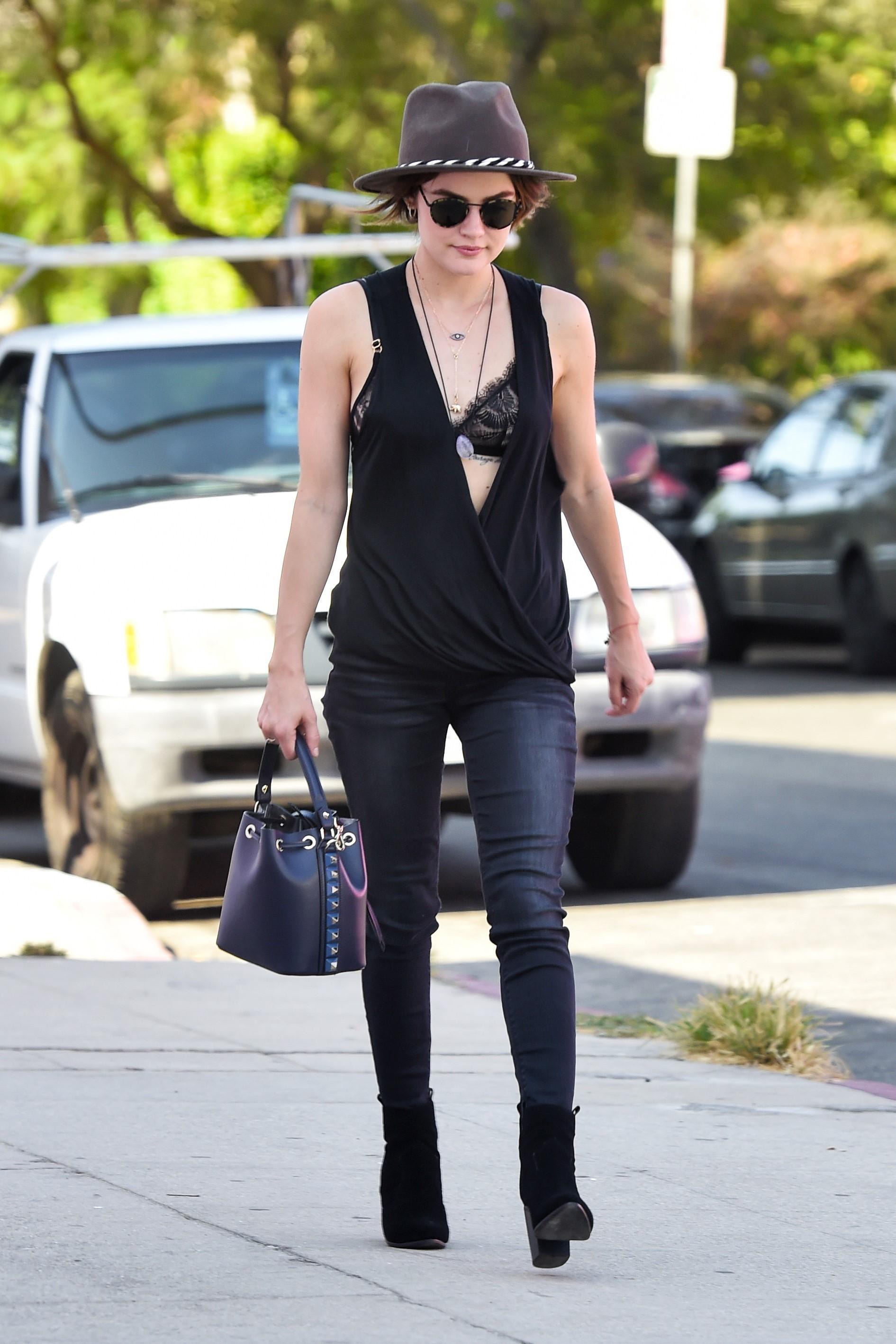 Lucy Hale com look todo preto e sutiã à mostra