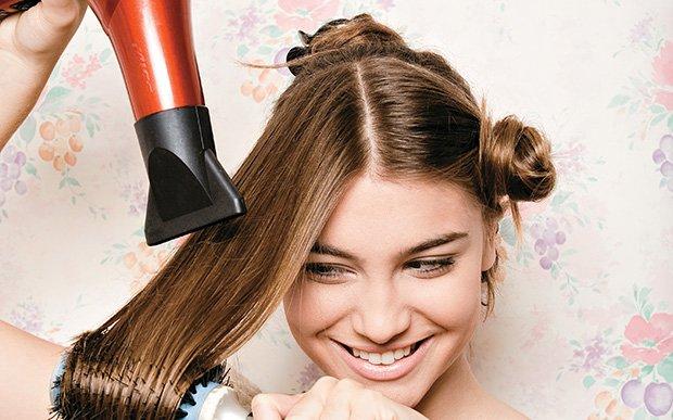 garota secando o cabelo com secador