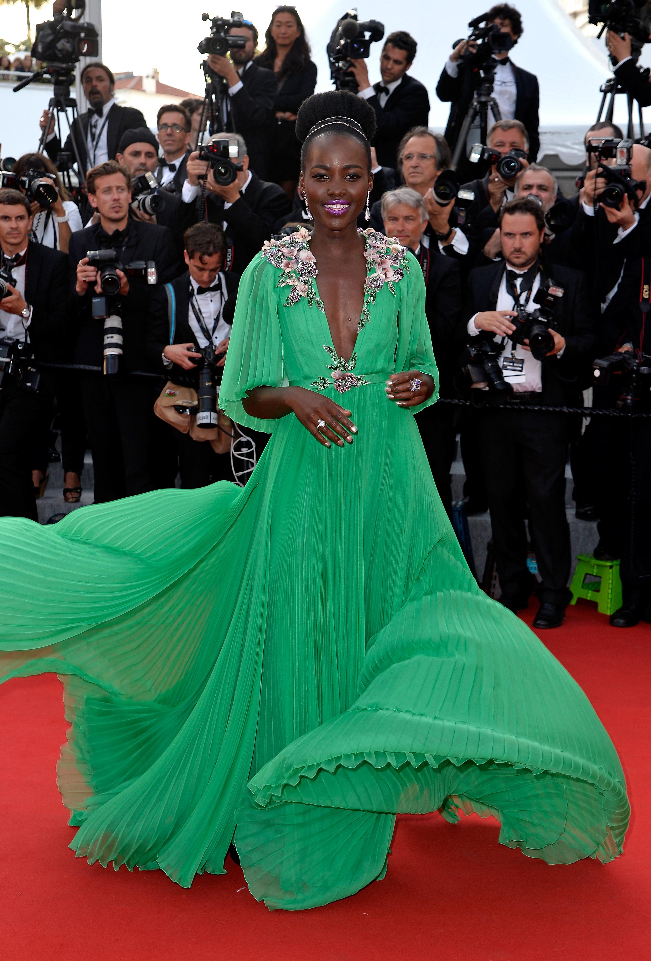 Lupita Nyong'o usando vestido verde longo com apliações florais