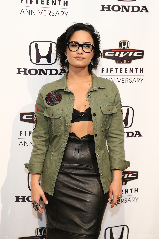Demi Lovato com óculos de grau, parca e sutiã à mostra