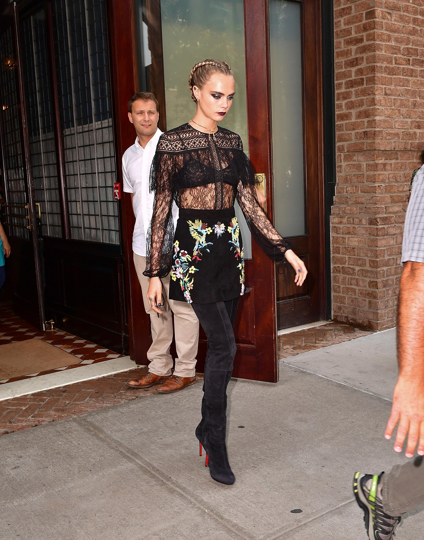 Cara Delevingne usa blusa de renda e saia floral bordada com bota over the knee