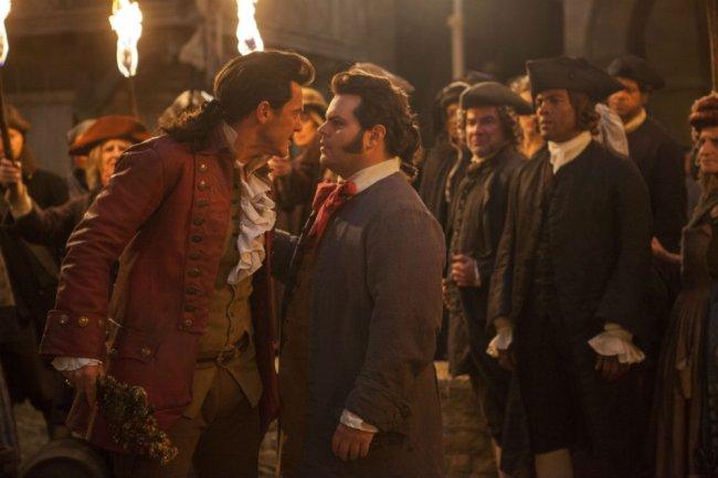 Gaston e Le Fou em cena de A Bela e a Fera; os dois estão se encarando no meio de uma multidão