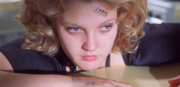 Mulher com a palavra loser tatuada na cara