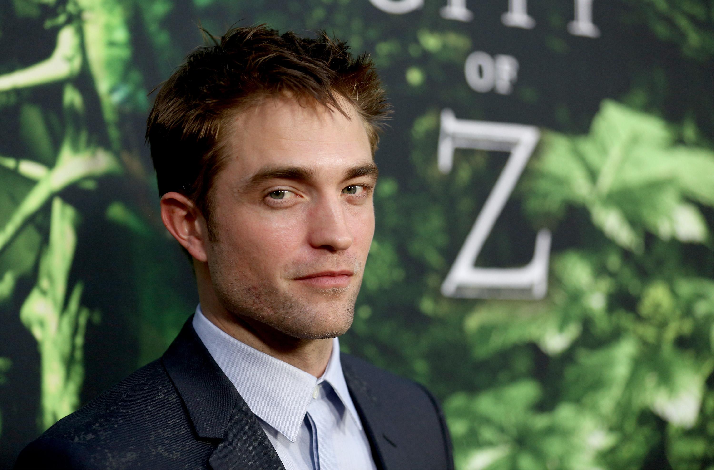 Robert Pattinson posando para foto em evento; o ator sorri levemente em um terno preto com camisa azul clara