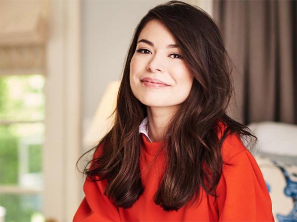Miranda Cosgrove posando para foto sorrindo levemente usando uma blusa vermelha e cabelo solto