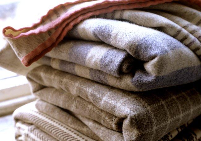 Imagem com alguns cobertores dobrados