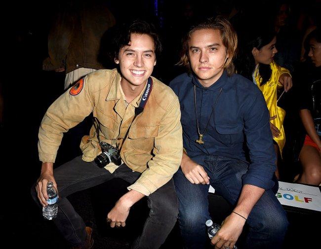 Cole e Dylan Sprouse em desfile do Made LA, em Los Angeles, em 2016; Cole sorri abertamente enquanto Dylan sorri levemente; os dois estão sentados e Cole está com o cabelo preto e Dylan loiro