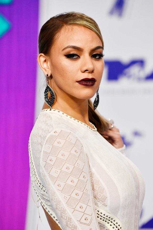 Dinah posando para foto no VMA; ela está olhando para a câmera por cima do ombro com expressão séria; usa uma roupa branca com batom escuro
