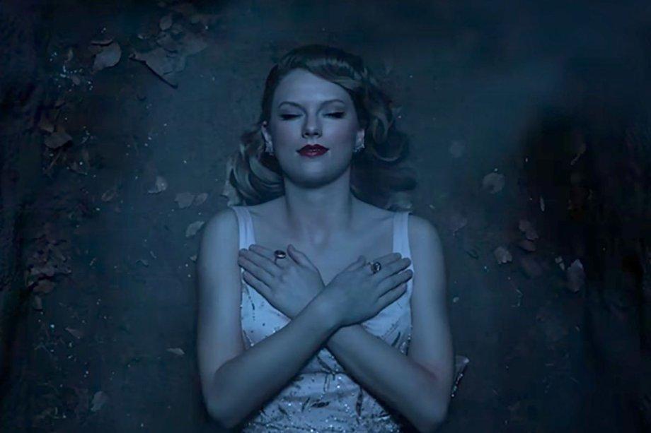 Na sequência, Taylor aparece ~plena~ em um túmulo. A maquiagem é clássica: batom vermelho, pele iluminada e delineador.