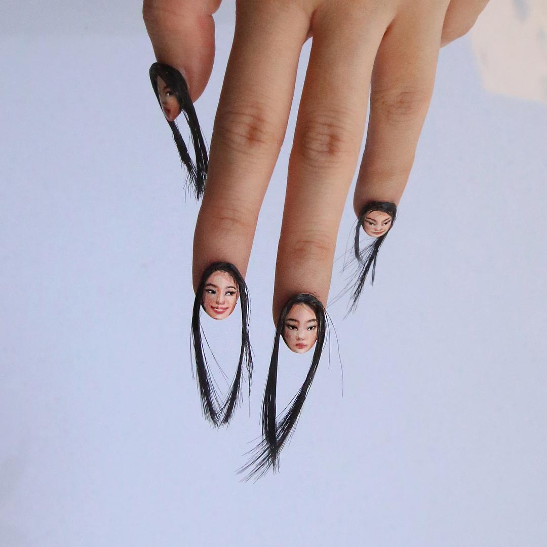 Na foto, aparece uma mão e as unhas possuem uma nail art com o rosto de uma pessoa e cabelos saindo delas.