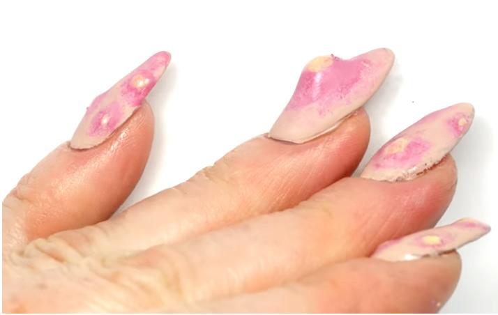 Foto mostra, em um fundo branco, unhas com nail art que imita espinhas.