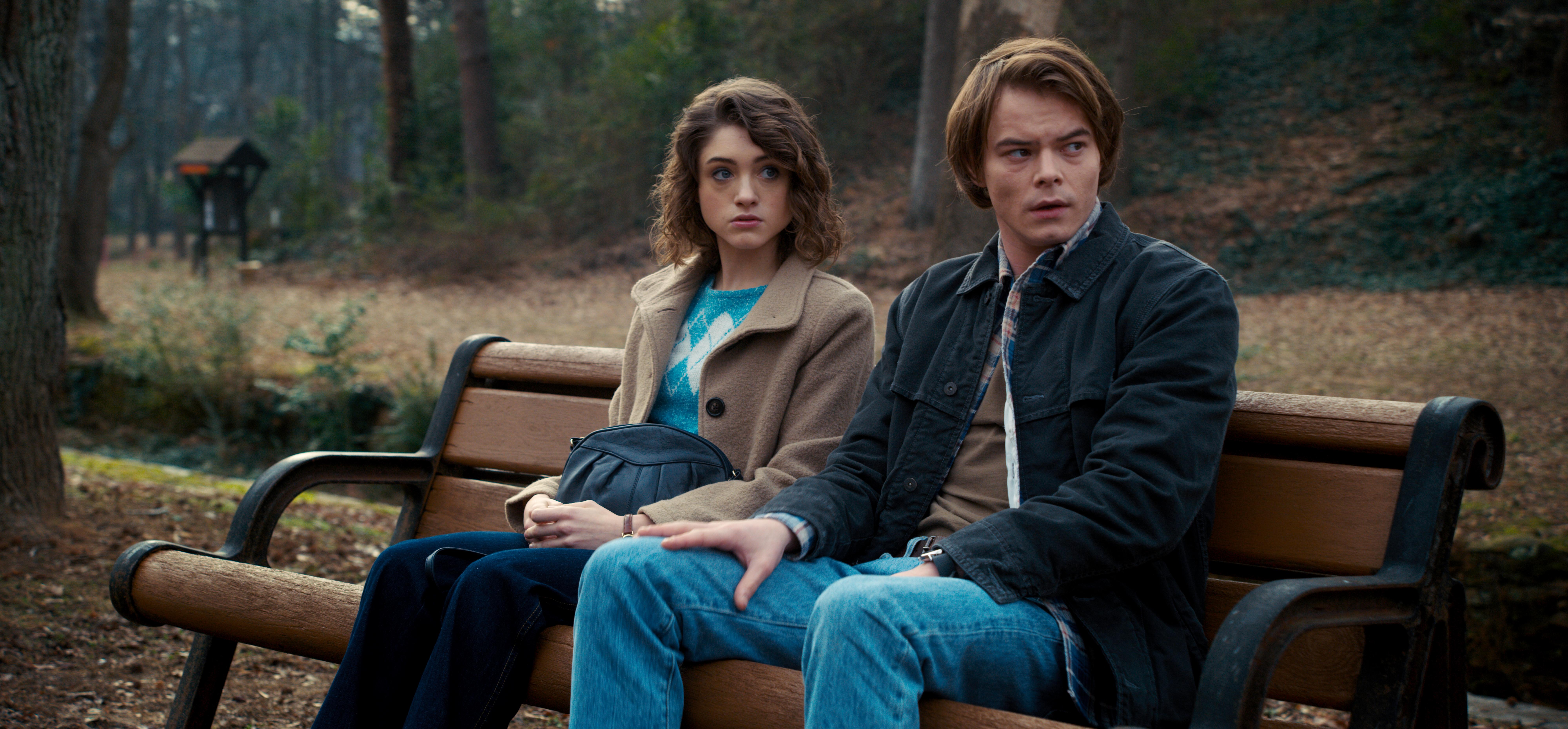 Nancy e Jonathan em Stranger Things sentados em um banco no parque