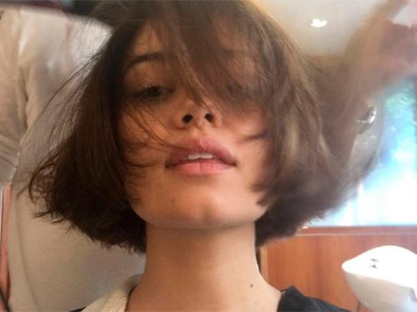 Sophie Charlotte posando para selfie com cabelo e franja cobrindo seu rosto