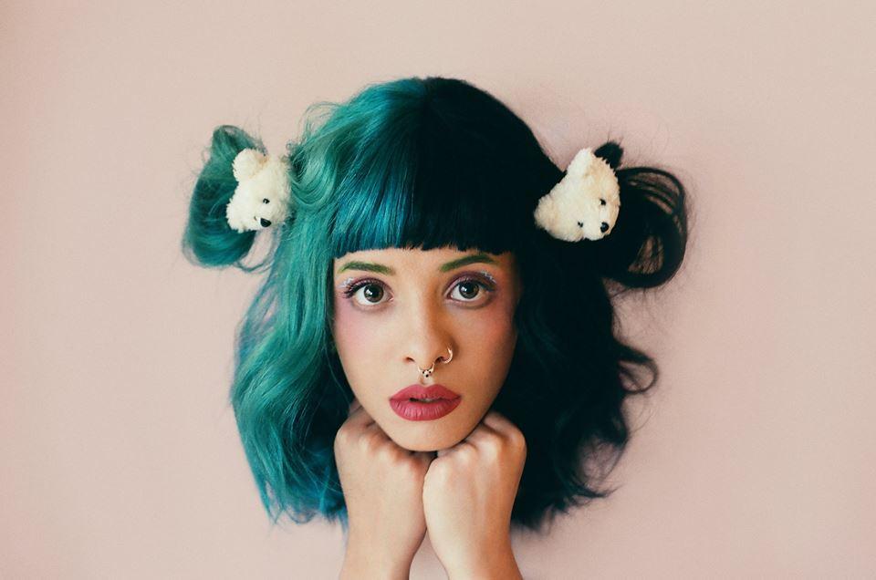 Melanie Martinez posando para foto com as duas mãos apoiadas no queixo; metade de seu cabelo em tons de verde e azul, outra metade preto