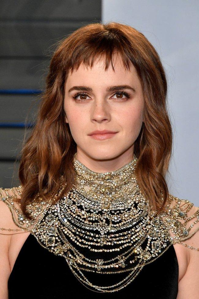 Emma Watson com expressão séria usando múltiplos colares.