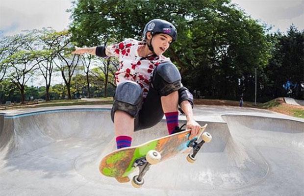 A imagem mostra uma menina branca, vestindo equipamento de proteção preto (capacete, joelheira e cutuveleira), fazendo uma manobra de skate numa pista de skate.