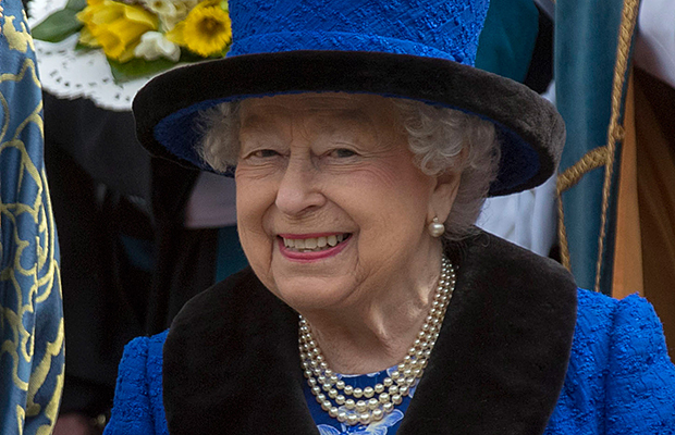 Rainha Elizabeth II usando joias de pérolas e um conjunto azul marinho com detalhes em preto, chapéu das mesmas cores, sorrindo abertamente para foto