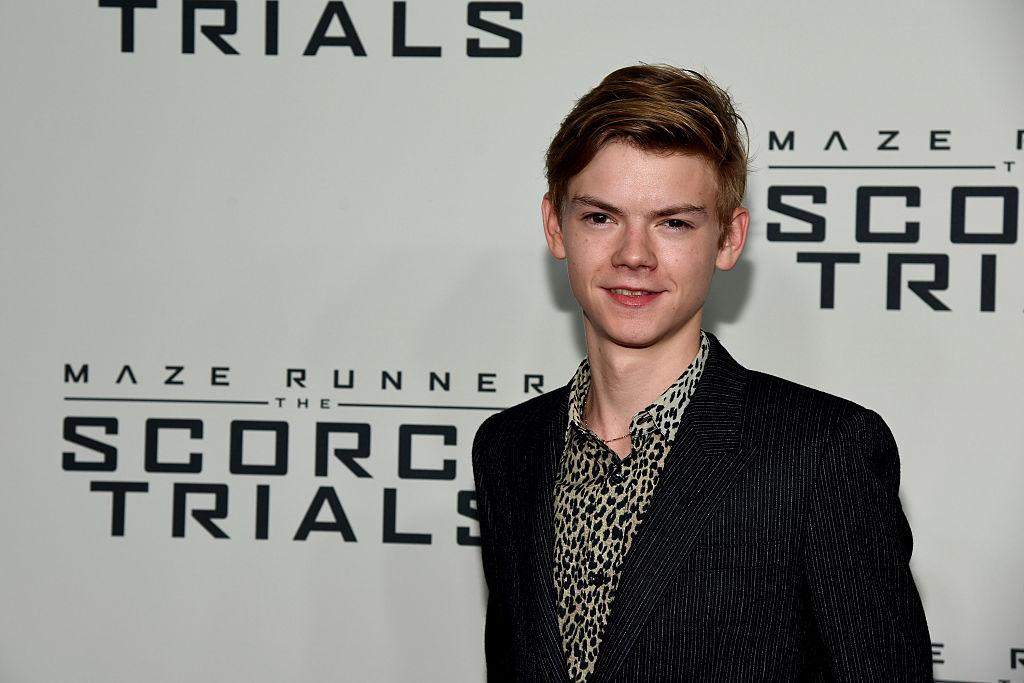 Thomas Brodie-Sangster posando em premiere de The Maze Runner; o ator usa um blazer preto e camisa com estampa de onça enquanto sorri