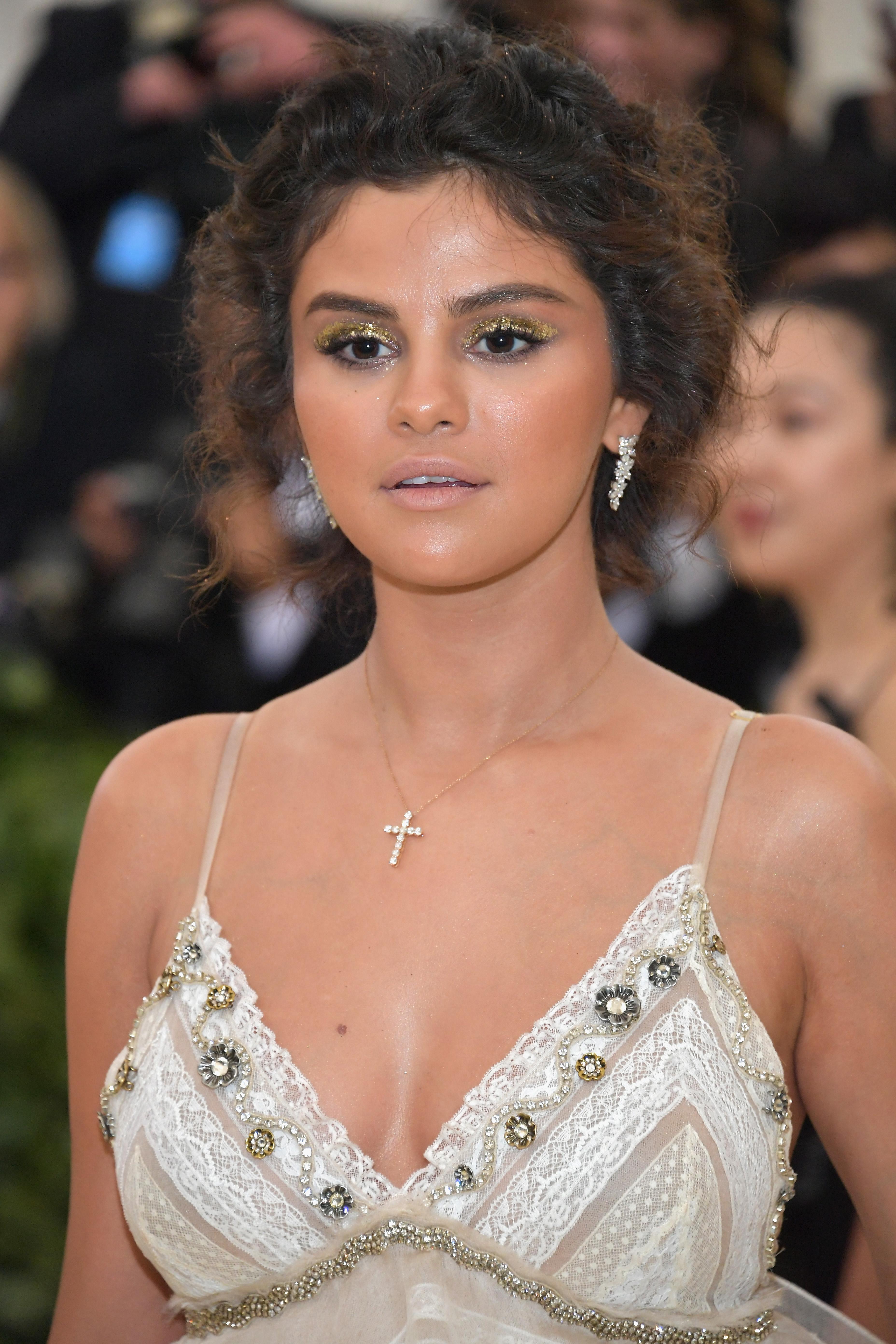Selena Gomez no MET Gala 2018 usando vestido de alcinha, colar de cruz e com expressão facial séria