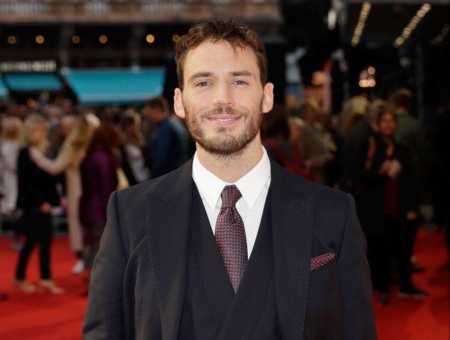 Sam Claflin no festival de filmes de Londres usando terno de três peças preto com camisa branca; ele está posando para foto e sorrindo levemente
