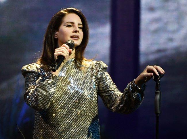 Lana Del Rey cantando no show em Mandalay Bay, em Las Vegas; ela usa uma roupa brilhante e olha para o público segurando o microfone em uma das mãos
