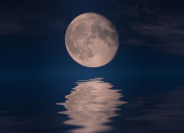 céu escuro, à noite. A imagem da Lua Cheia está refletida sobre águas