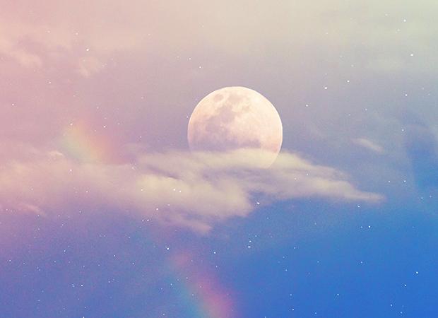 céu azulado com um arco íris. Atrás de uma das nuvens está uma lua cheia parcialmente coberta