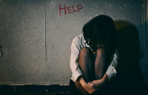 Garota sentada no chão, com as pernas encolhidas, o rosto entre elas, num pedido de ajuda