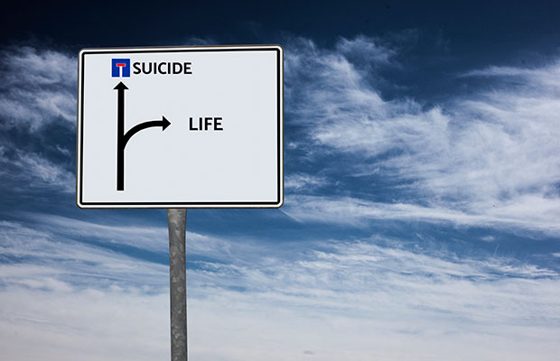 Imagem mostrando uma placa de trânsito com os destinos: suicídio e vida