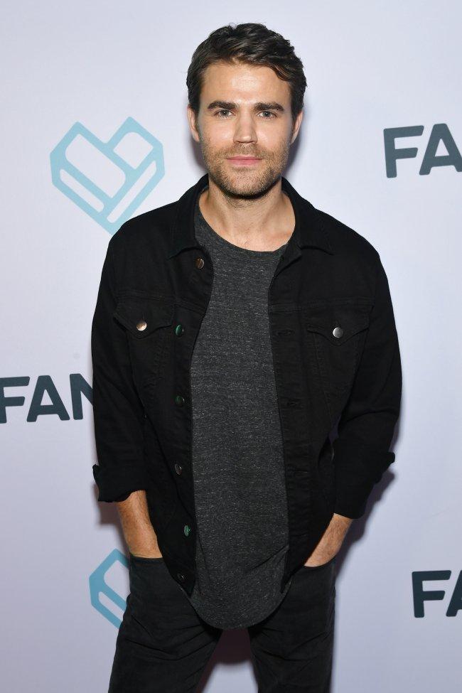 Paul Wesley posando para foto no carpet da Comic Con em 2018, ele usa camiseta, calça e jaqueta de cor preta e sorri levemente