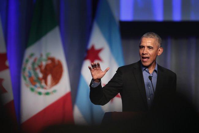 Barack Obama com a mão levantada enquanto fala em discurso; ele usa terno preto com uma camisa azul