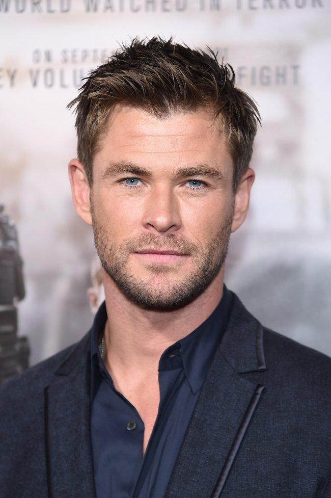 Chris Hemsworth posando para foto; ele está com terno preto e camisa azul-escuro com expressão neutra