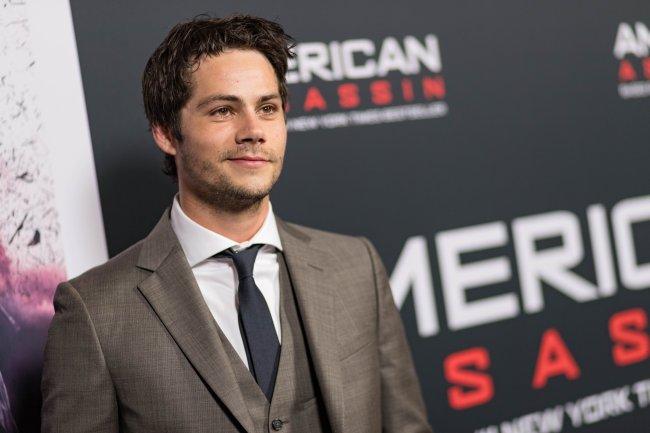 Dylan O'Brien posando para foto em carpet de evento com terno marrom, camisa branca e gravata preta; o ator sorri levemente