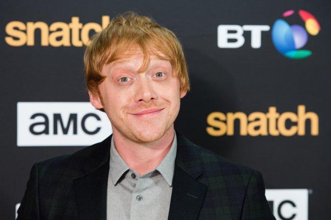 Rupert Grint em carpet de premiere sorrindo levemente para a câmera e arregalando os olhos; ele usa uma camisa cinza com blazer escuro