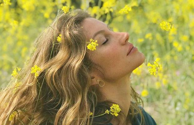 Foto de Gisele rodeada por flores amarelas; ela está de olhos fechados inclinando a cabeça e algumas flores estão em seu rosto