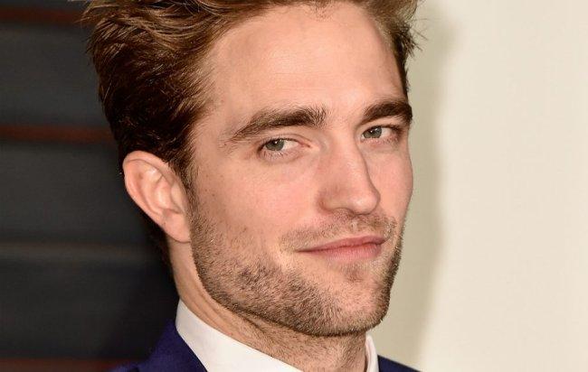 Foto com close no rosto de Robert Pattinson; o ator sorri levemente com barba curta enquanto olha para o lado