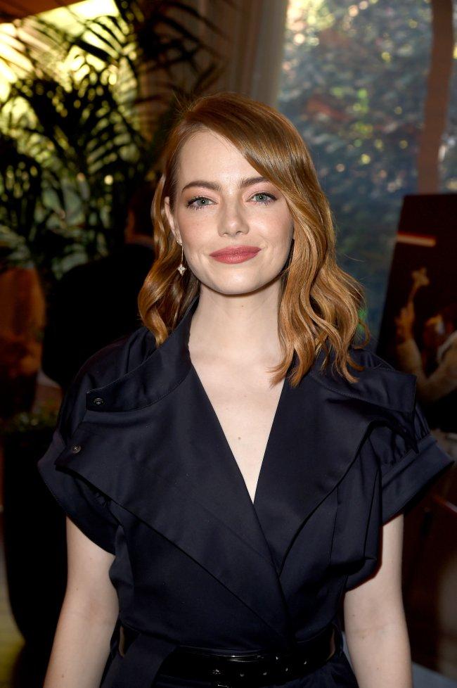 Emma Stone posando para foto; ela está olhando para câmera de frente com o cabelo solto, roupa preta de decote V com cinto da mesma cor e sorri levemente