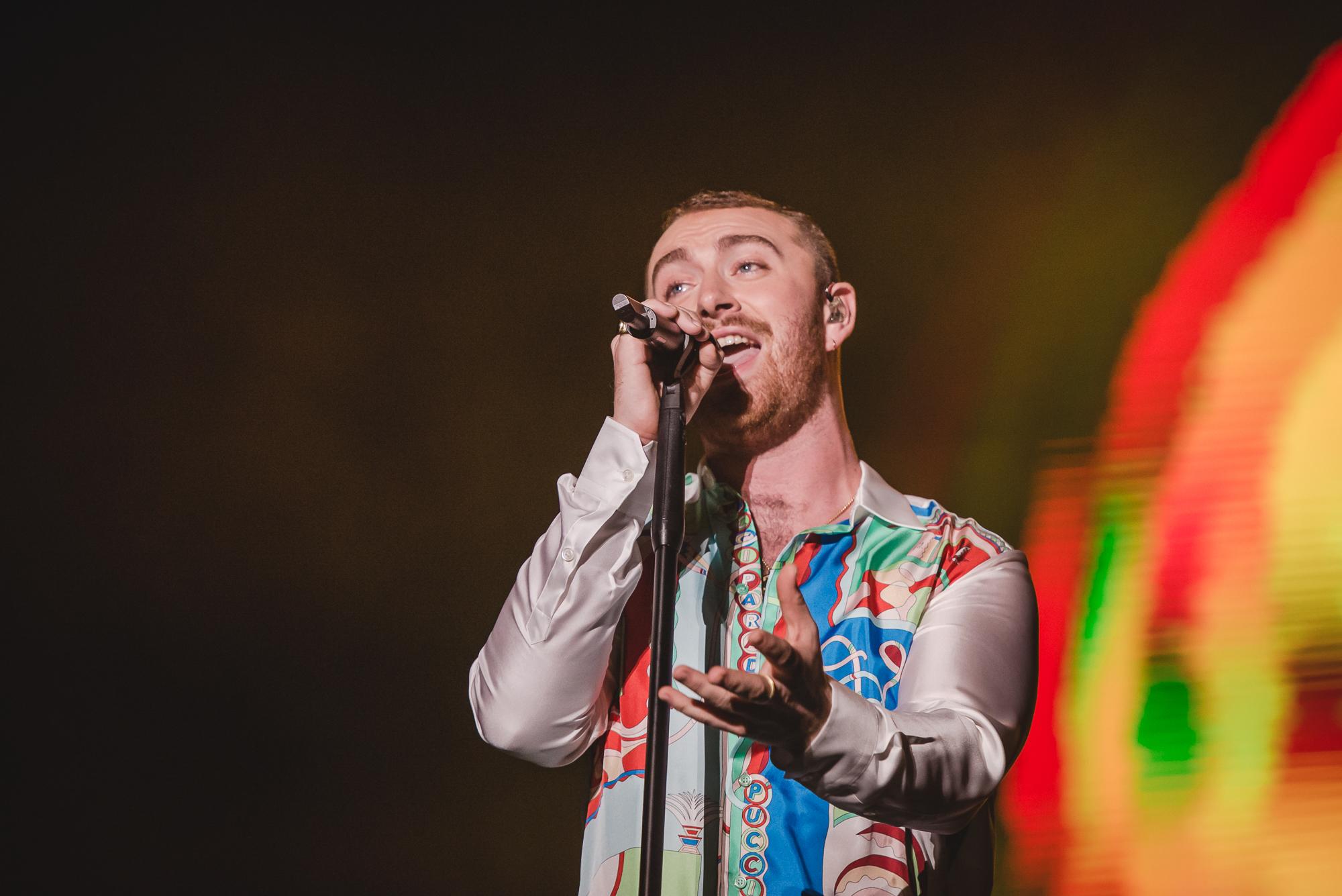 Sam Smith no palco do Lollapalooza Brasil; o cantor segura a base do microfone com uma mão e estende a outra na direção do público; ele olha para frente e luzes coloridas iluminam o fundo do palco
