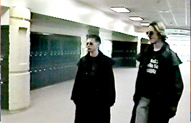 Imagens do Massacre de Columbine; assassinos são dois jovens; eles usam sobretudos preto e óculos escuros