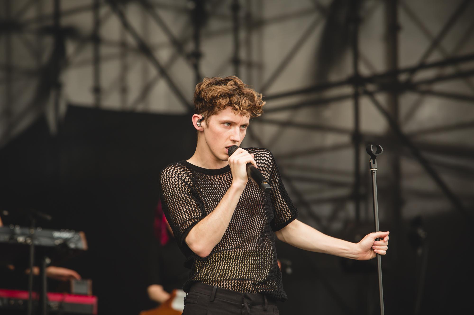 Troye Sivan cantando no palco do Lollapalooza Brasil; ele usa uma camisa preta transparente com furinhos e está observando o público enquanto canta segurando o microfone próximo do rosto