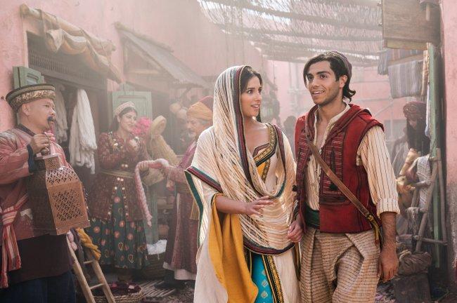 Naomi Scott e Mena Massoud são Jasmine e Aladdin no live-action da animação da Disney; na foto eles estão caracterizados como os personagens e andando na rua; Jasmine olha para Aladdin com expressão curiosa e ele está olhando pra frente e sorrindo