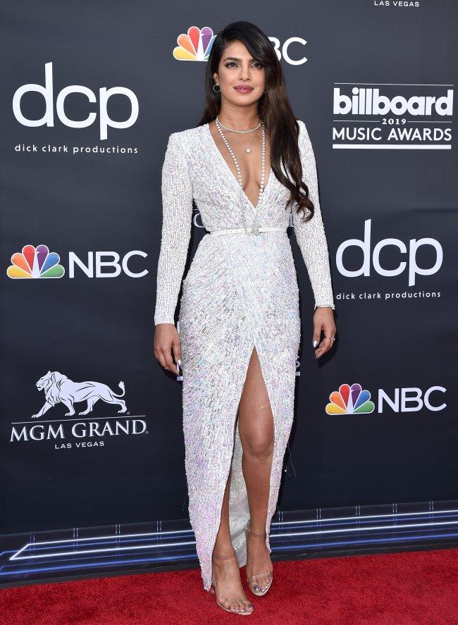 Priyanka Chopra posando no carpert do Billboard Music Awards 2019 com vestido todo branco com fenda