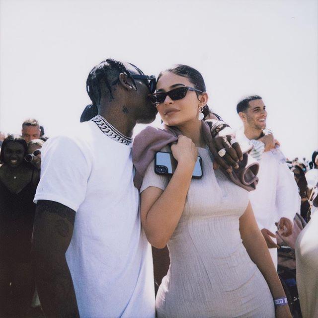 Kylie Jenner e Travis Scott posando para foto; Travis está usando uma camiseta branca enquanto dá um beijo na bochecha de Kylie com o braço ao redor do pescoço da empresária que usa um vestido claro com óculos de sol e sorri levemente
