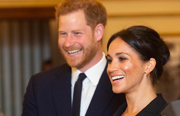 Príncipe Harry e Meghan Markle de perfil; os dois estão sorrindo observando algo; Harry usa um terno e gravata preta com camisa branca e Meghan usa roupa preta com cabelo preso